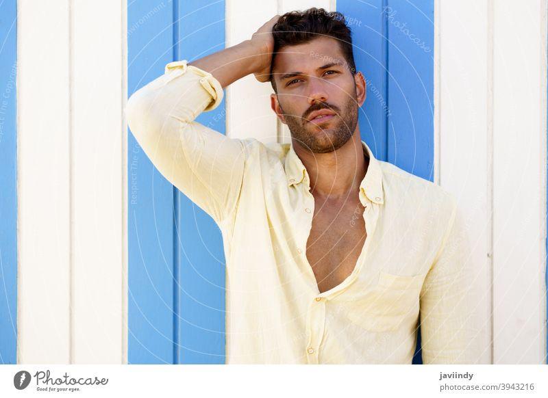 Junger Mann, Modemodell, posiert vor einer Strandbude. Frisur Sommer modisch Vollbart Model Blick Person Typ jung Hemd gutaussehend Porträt Hintergrund