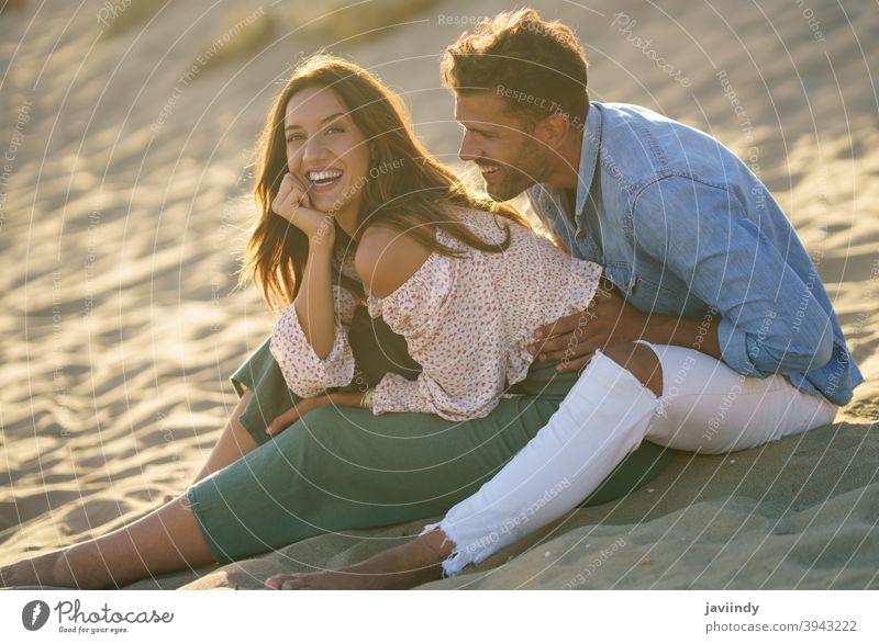 Junges Paar lachend zusammen sitzen auf dem Sand des Strandes Lachen Lächeln Frau Mann Sitzen Erwachsener Person Urlaub Kaukasier Dame Glück Mädchen Feiertag