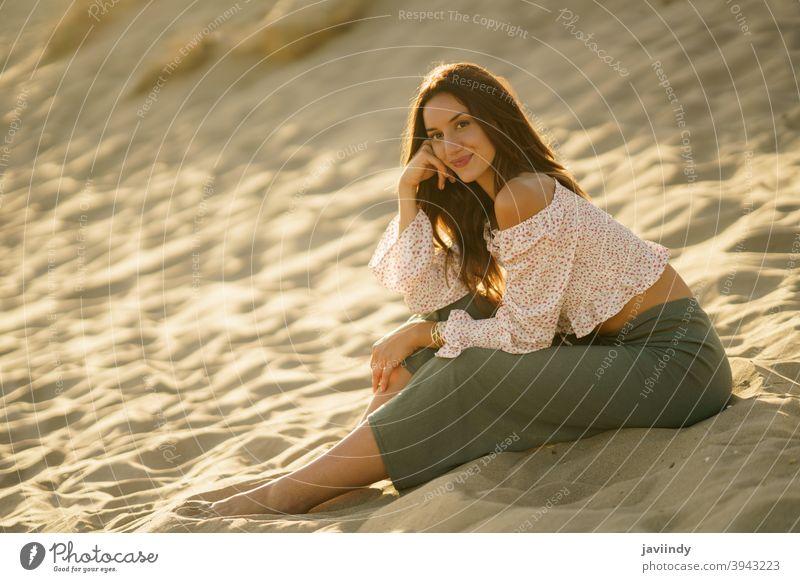 Attraktive Frau sitzt auf dem Sand des Strandes Sitzen Erwachsener Person Urlaub Kaukasier Dame Mädchen Feiertag sich[Akk] entspannen außerhalb jung reisen