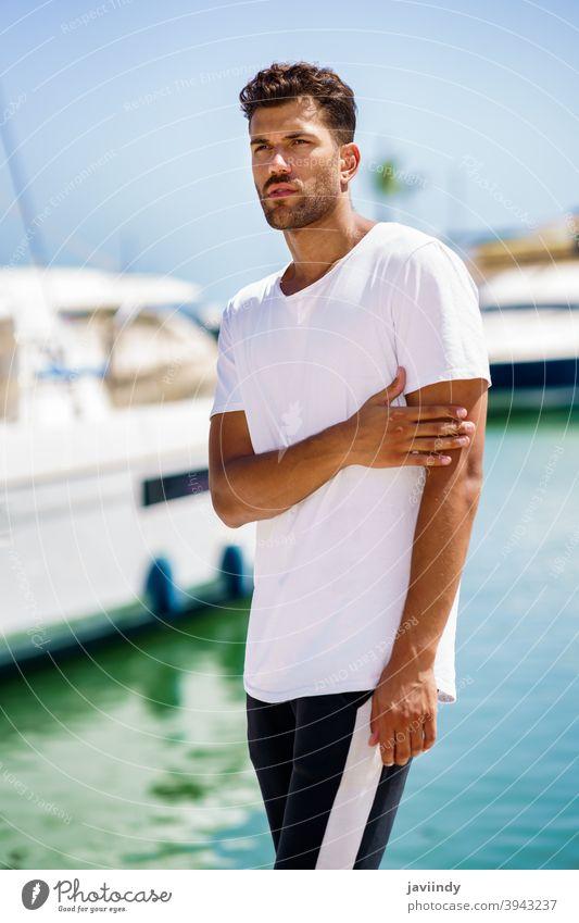 Fitness-Model in Sportswear-Outfit posiert am Hafen. Mann passen Aktivität jung Freizeit Kaukasier Sportbekleidung Lifestyle Person im Freien sportlich weiß