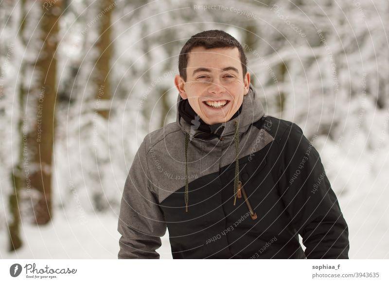 Winter - glücklicher junger Mann hat Spaß im Schnee und lacht, lächelt in die Kamera Porträt Lächeln Lachen Teenager Fröhlichkeit Glück Freude Junge Typ kalt