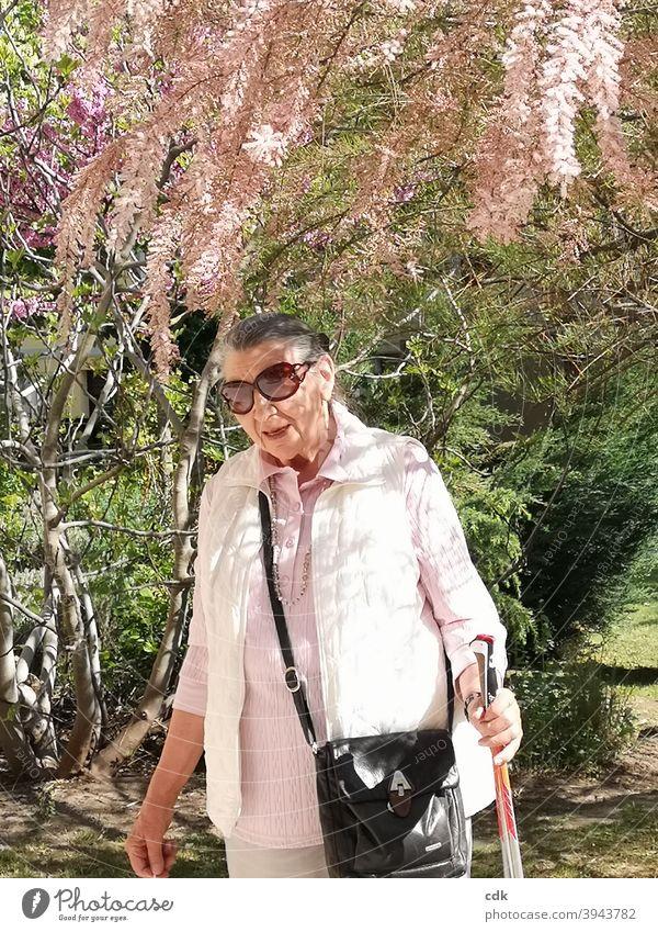 frühlingshaft Frau Mensch Seniorin 80+ spazieren Spaziergang Sonne Sonnenschein Frühling blühen blühender Baum rosa zart anmutig weiblich elegant Dame