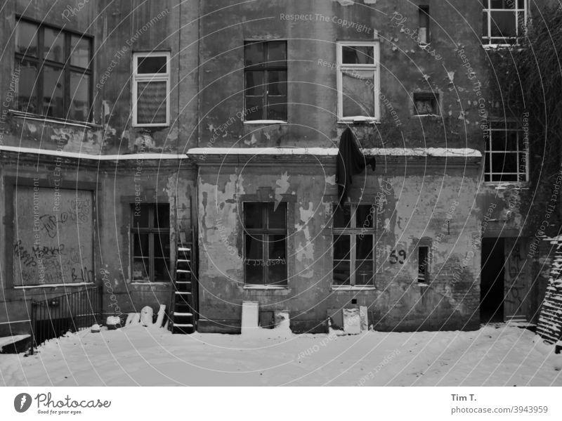 ein verschneiter alter Hinterhof in Prenzlauer Berg Berlin s/w b/w Winter Schnee Altbau Schwarzweißfoto Architektur b&w Fenster Außenaufnahme schwarz Tag