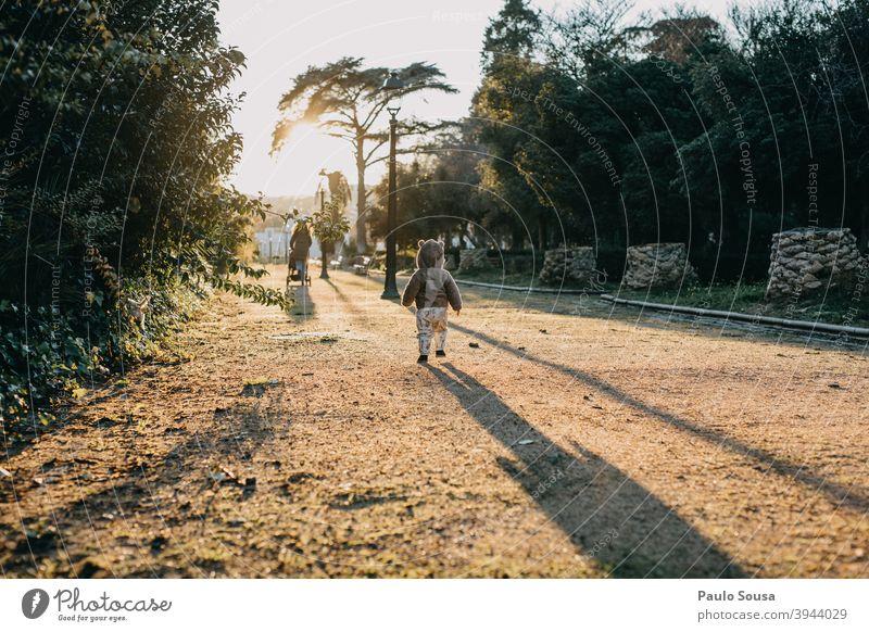 Rückansicht Kleinkind zu Fuß auf dem Park Sonnenuntergang gegen Tag Freude Kind Mensch Farbfoto Außenaufnahme 1-3 Jahre Kindheit Kinderspiel Fröhlichkeit