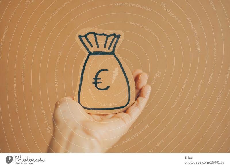 Eine Person hält einen gemalten Geldsack in der Hand Konzept Geldgeber und Spende. geben bekommen Finanzen Investition sparen Erspartes Euro Reichtum Vermögen