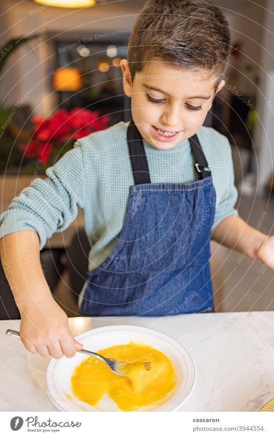 Kleiner Junge, der ein Ei in der Küche schlägt Aktivitäten backen schlagen schlagend Kekse Schalen & Schüsseln Kuchen Küchenchef Kind Kindheit Kinder Koch