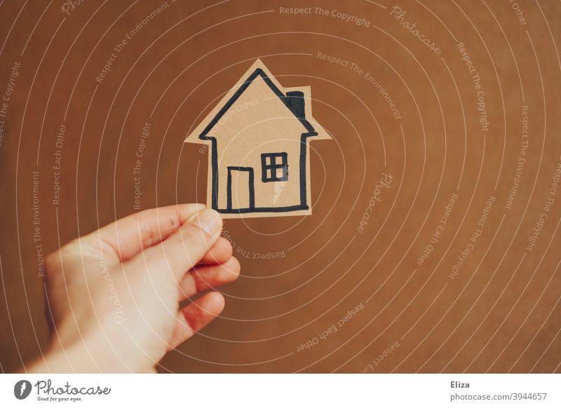 Hand hält ein kleines gemaltes Hau. Konzept Hausbau und Eigenheim. zuhause Haus bauen Umzug Wohnraum Bausparen Immobilie Makler häuslich Wohneigentum wohnen