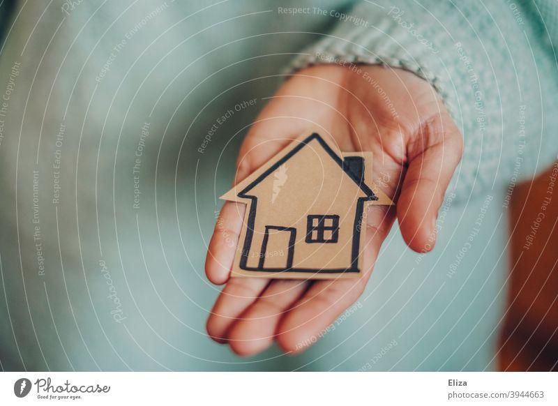 Hand hält ein kleines gemaltes Haus in den Händen. Konzept Hausbau und Eigenheim. zuhause Haus bauen Umzug Wohnraum Bausparen Immobilie Makler häuslich