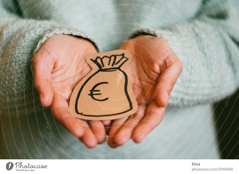 Eine Person hält einen gemalten Geldsack in den Händen. Konzept Geldgeber und Spende. geben bekommen Finanzen Investition sparen Erspartes Euro Reichtum