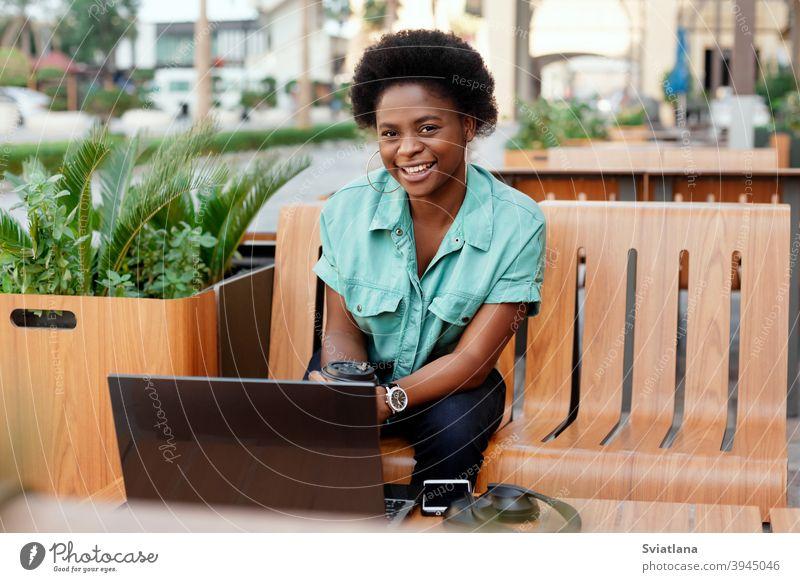 Porträt eines jungen afrikanischen Mädchens, das in einem Café während einer Kaffeepause an einem Laptop arbeitet. Eine Pause, entspannen, online arbeiten, freiberuflich