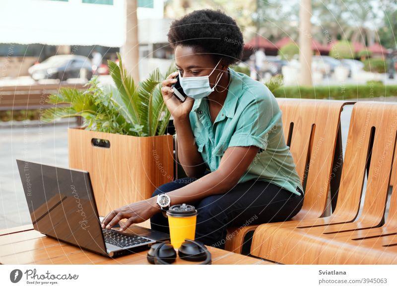Ein junges afrikanisches Mädchen mit einer medizinischen Gesichtsmaske telefoniert und arbeitet mit einem Laptop an einem Tisch in einem Café. Soziale Distanzierung und Arbeit, Arbeit online, Business online