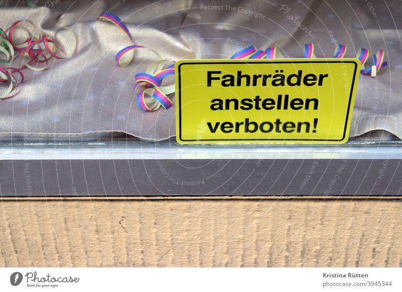 fahrräder anstellen verboten schild im schaufenster mit luftschlangen deko abstellen verbotsschild hinweis hinweisschild laden geschäft dekoration partydeko