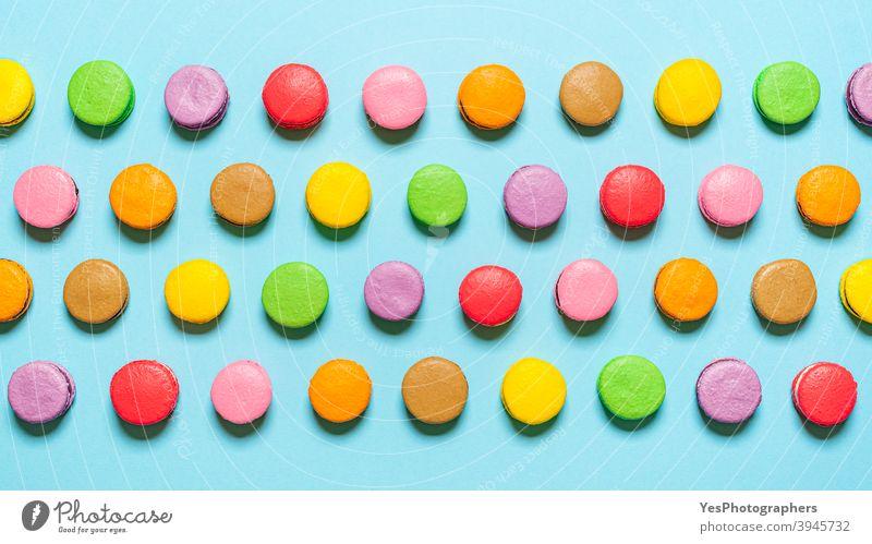 Mehrfarbige hausgemachte Macarons flach legen. Draufsicht mit in einer Reihe angeordneten Macarons obere Ansicht ausgerichtet Mandelplätzchen Handwerklich