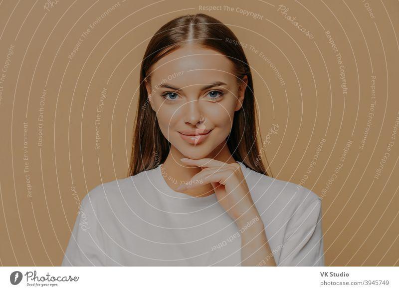 Schöne junge europäische Frau mit Make-up gesunde Haut berührt sanft Kieferlinie schaut direkt in die Kamera hat lange geraden Haare natürliche Schönheit in lässigen Pullover gekleidet isoliert über braunen Hintergrund