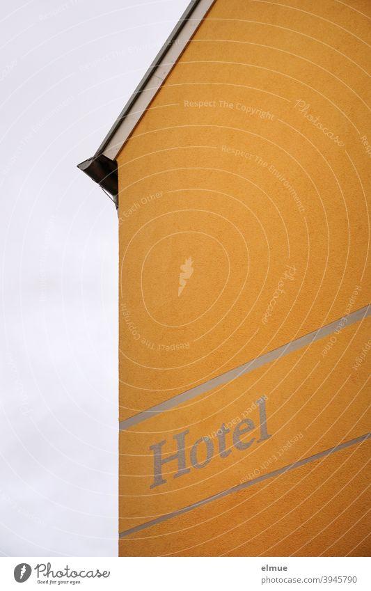 """Seitenansicht eines gelben Gebäudes ohne Fenster und mit der Aufschrift """"Hotel"""" / Beherbergungsverbot / Übernachten coronakrise Prävention Schutz Übernachtung"""