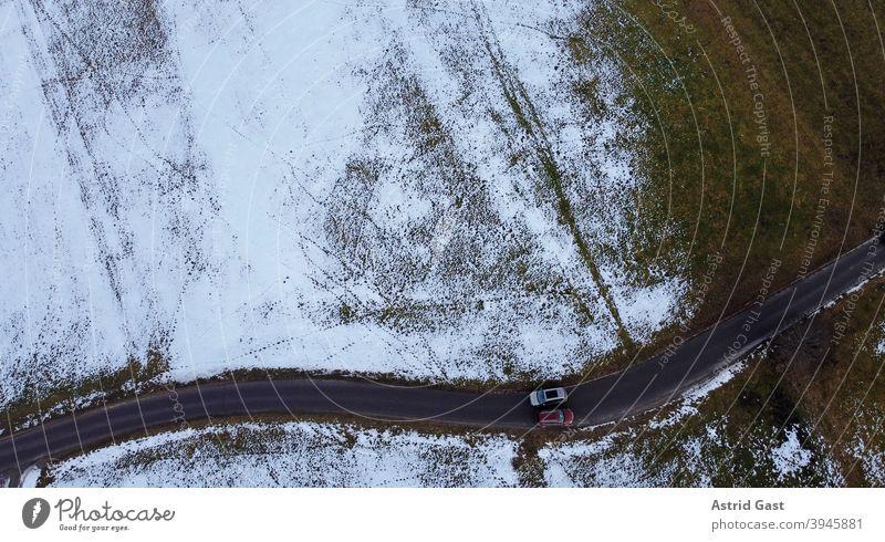 Drohnenfoto von zwei Autos die im Winter auf einer engen Straße aneinander vorbeifahren luftaufnahme drohnenfoto auto winter straße schnee sonne schatten licht