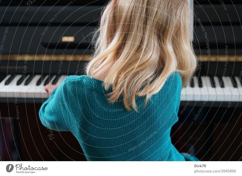 Kleine Pianistin - Rückansicht eines blonden Mädchens beim Klavierspiel Kind Kindheit Musik Musikerin Klavierspielen klavierspielerin Klaviatur Innenaufnahme