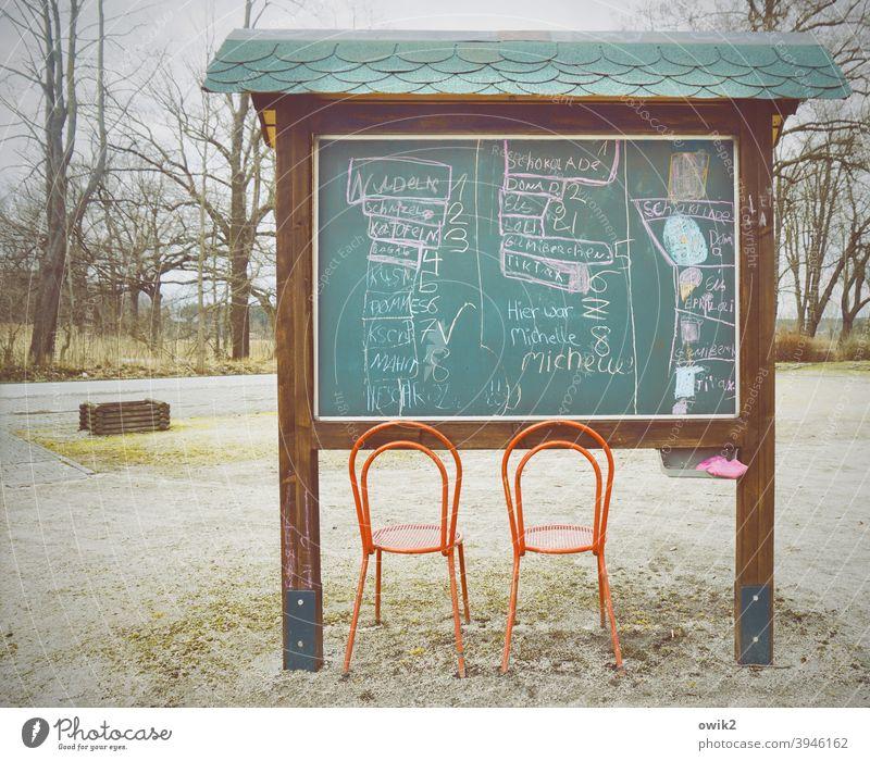 Dorfkino skurril Infotafel Stühle nah Platz nehmen Kino einfach Bäume Tafel Zeichnungen Buchstaben kryptisch rätselhaft Szene Sitzgelegenheit leer Menschenleer