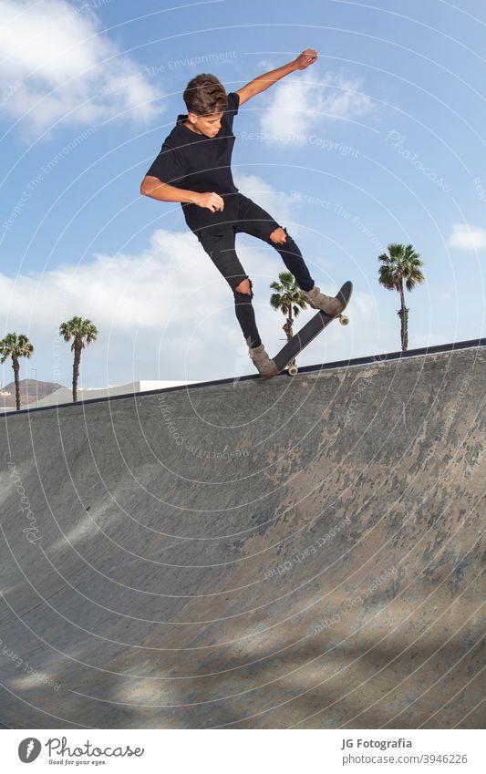 Junger Skateboarder führt Tricks in einem Park aus, mit Straßenhintergrund und blauem Himmel. jung springen Großstadt Lifestyle Stunt männlich Aktion aktiv Spaß