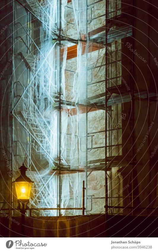 beleuchtetes Baugerüst an Kirche Baustelle Neonröhre Treppe Winter laterne nacht nachts Gerüst Fassade Menschenleer Gebäude Außenaufnahme Sanieren Architektur