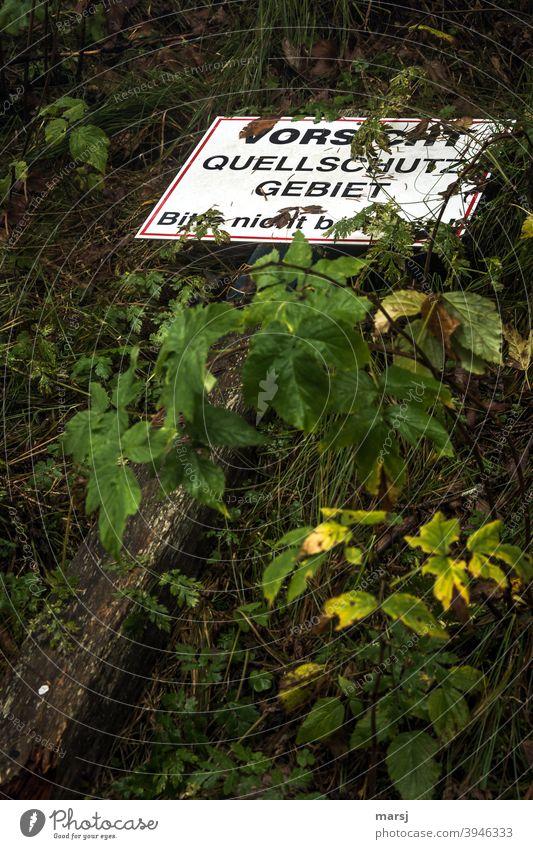systemrelevant | Trinkwasser. Quellschutzgebiet, geschützt durch eine Warntafel, die aber am Boden liegt. Hinweisschild Verbotsschild Einschränkung
