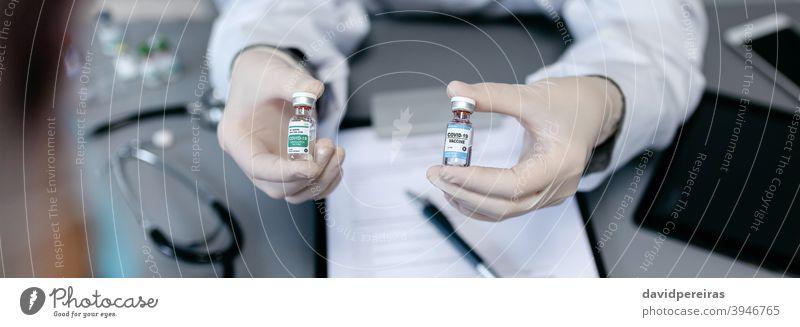 Ärztin zeigt ihrer Patientin zwei verschiedene Coronavirus-Impfstoffe opt unkenntlich Arzt zeigend Optionen Alternativen covid-19 vergleichen Angebot