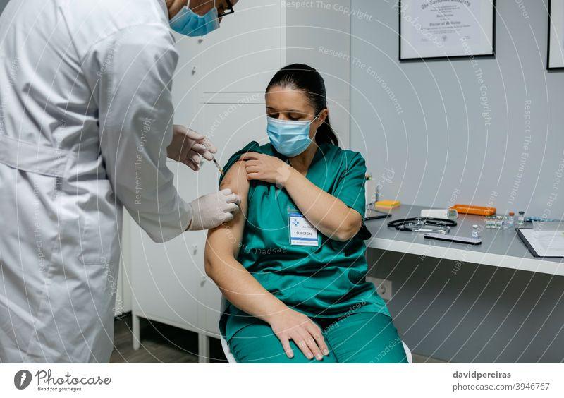 Chirurgin erhält Impfstoff gegen Coronavirus Impfung Gesundheitspersonal covid-19 Einspritzung Arzt Klinik medizinisch Medizin professionell Arztpraxis