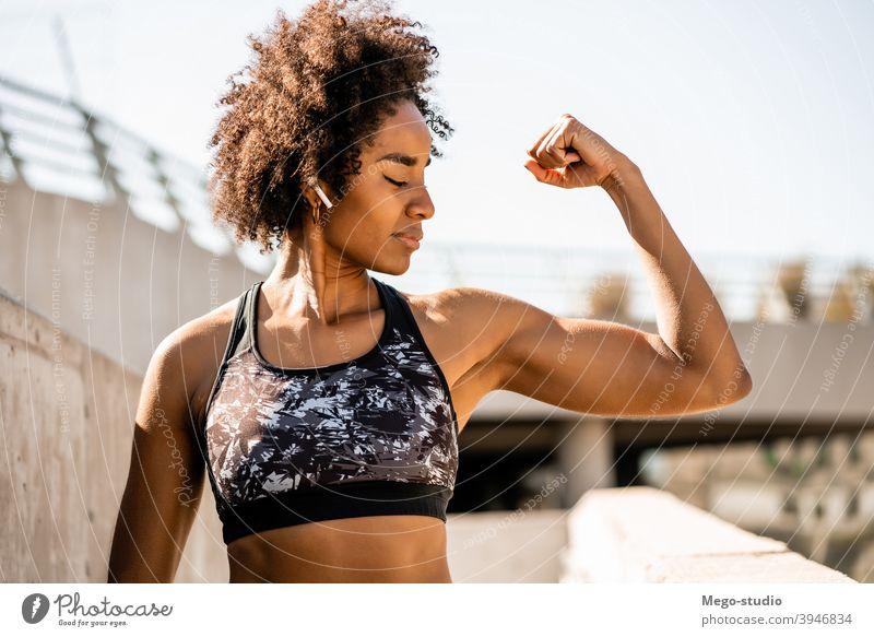 Afro-Athlet Frau flexing und zeigt Muskeln. Fitness Sport Übung aussruhen Pause im Freien sich[Akk] entspannen genießend Erholung Freizeit Ohrstöpsel sportlich