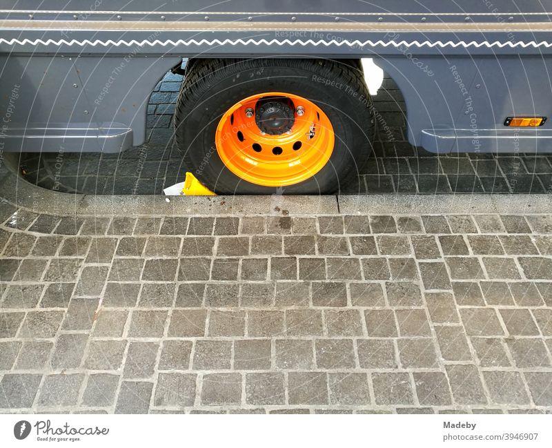Foodtruck in Blau mit Felge in leuchtendem Orange am Bordstein eines gepflasterten Bürgersteigs Food Truck Imniss Gehweg Streifen Verzierung Dekor Lieferwagen