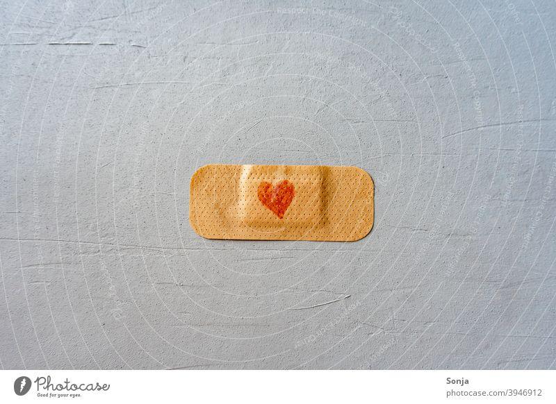 Ein Pflaster mit Herz auf einem grauen Hintergrund herzförmig rot Impfung Gesundheit Virus Krankheit Krankenhaus Impfstoff medizinisch Behandlung Coronavirus