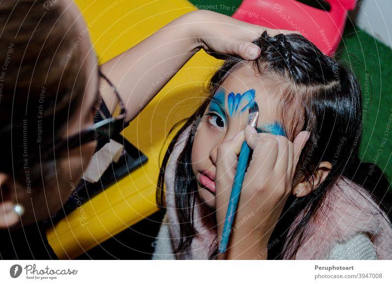 Kind Gesicht Kunst gemacht, um kleines Mädchen. Party Make-up Schmetterling Spaß wenig Glück Kaukasier Porträt jung Geburtstag Farbe Künstler blau Kindheit