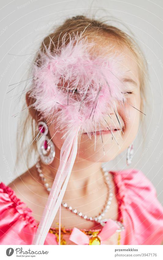 Kleines Mädchen genießt ihre Rolle der Prinzessin. Adorable niedlichen 5-6 Jahre altes Mädchen trägt rosa Prinzessin Kleid hält Zauberstab Fee Kind Stadtfest