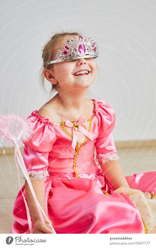 Kleines Mädchen genießt ihre Rolle der Prinzessin. Adorable niedlichen 5-6 Jahre altes Mädchen trägt rosa Prinzessin Kleid und Tiara Fee Kind Stadtfest