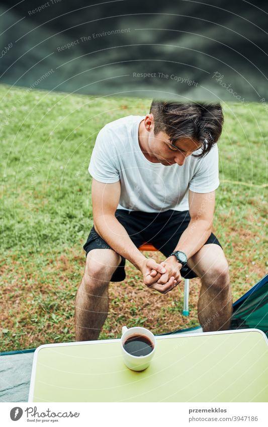 Junger Mann trinkt einen Kaffee sitzend vor dem Zelt am Morgen Abenteuer Getränk Pause Frühstück Lager Camping Nahaufnahme Tasse trinken Erkundung Freiheit