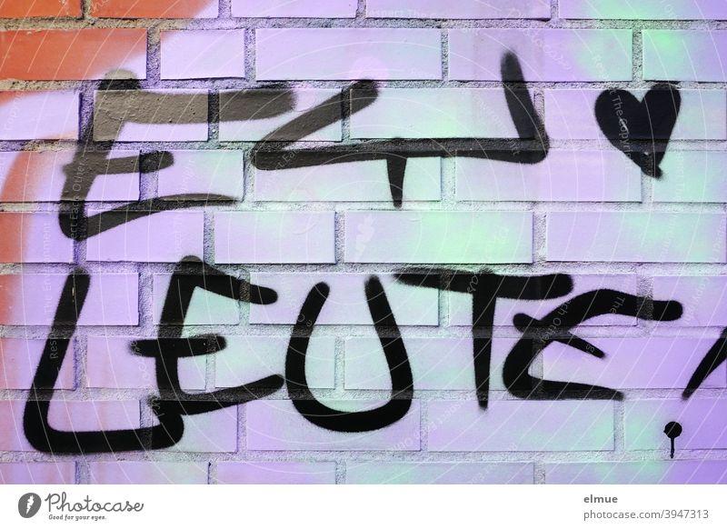 """Ein kleines Herz und """"EY LEUTE !"""" sind in schwarz auf eine grün-lila Ziegelwand gesprayt / Graffito / Jugendsprache / Lifestyle Ey Leute Graffiti sprayen"""
