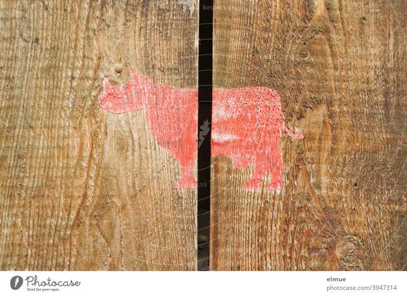 Fantasiewesen - halb Nashorn, halb Kuh - in rot über zwei, durch einen Spalt getrennte Naturholzlatten gemalt / Fabelwesen fantasiewesen Holz Holzlatten braun