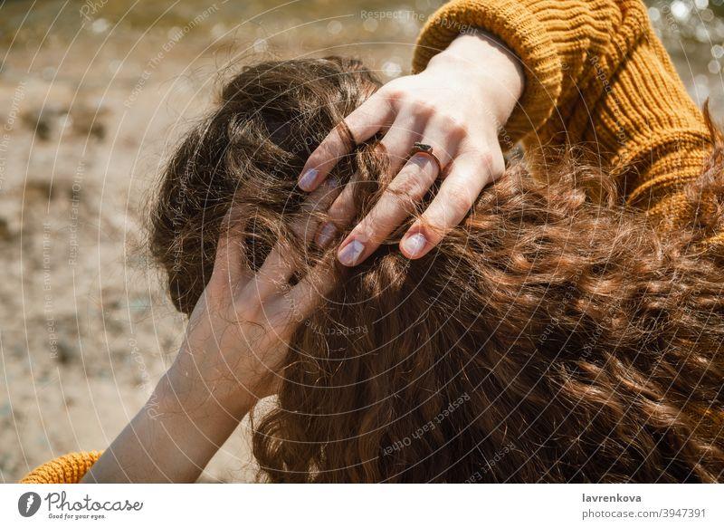 Draufsicht auf weibliche Hände, die dunkle lockige Haare hinter ihrem Kopf im Freien halten Frau brünett Mädchen Lifestyle Erwachsener Finger Flechten jung