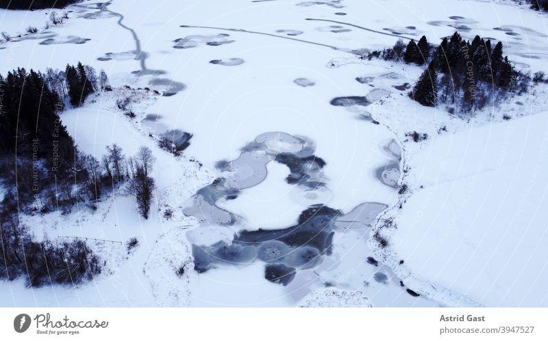 Luftaufnahme mit einer Drohne von einem zugefrorenen See in Bayern luftaufnahme drohnenfoto see gewässer eis winter schnee wasser kreise formen eisschicht