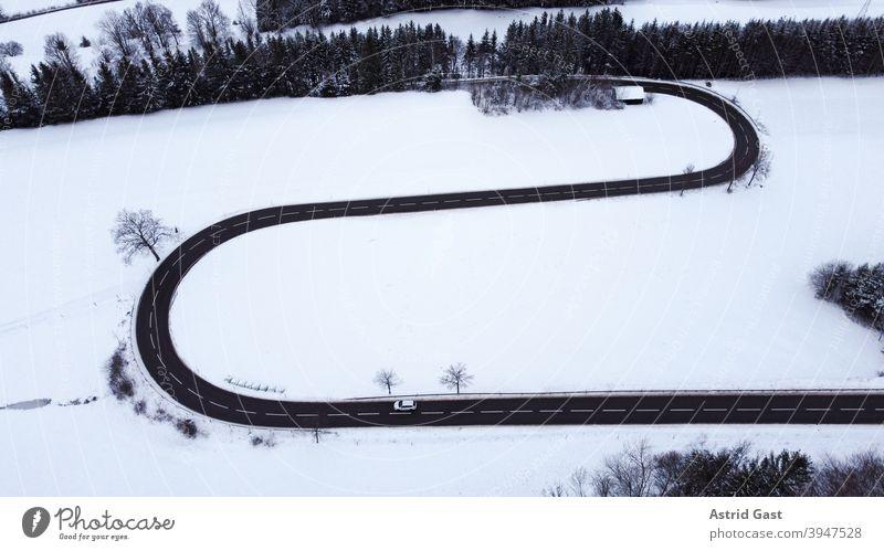 Luftaufnahme mit einer Drohne von einer Straßenkurve mit einem fahrenden Auto im Winter luftaufnahme drohnenfoto auto winter straße schnee kehre straßenkurve