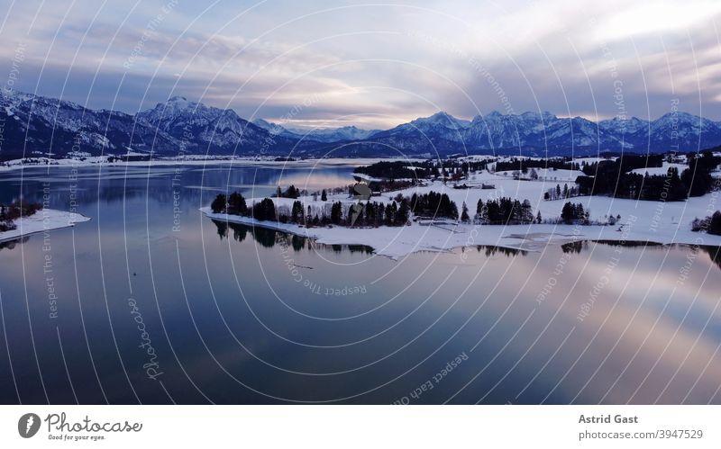 Luftaufnahme mit einer Drohne vom Forggensee im Allgäu im Winter in der blauen Stunde luftaufnahme drohnenfoto forggensee gewässer bayern allgäu stausee winter
