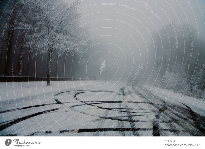 Reifenspuren auf einer glatten Straße mit Schnee und Eis Bäume Wald Weg Winter Auto Scheinwerferlicht Spuren glatteis asfalt asfaltstraße Menschenleer kalt PKW