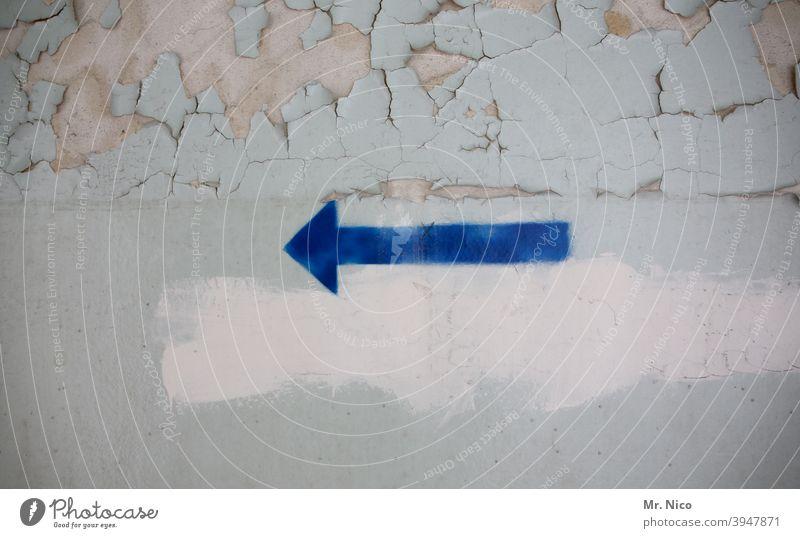 blauer Pfeil auf Wand Richtung richtungweisend Orientierung Zeichen Ziel nach links abblättern Mauer grau Renovieren dreckig Symbole & Metaphern Betonwand