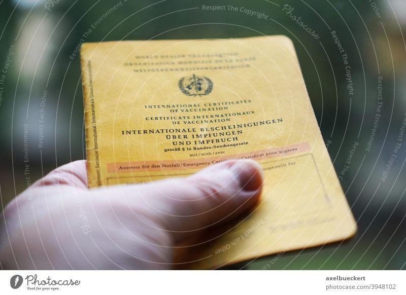 Hand hält Internationale Bescheinigungen über Impfungen und Impfbuch Impfpass Gesundheit Krankheit Medizin Impfstoff Virus Gesundheitswesen Coronavirus Pandemie