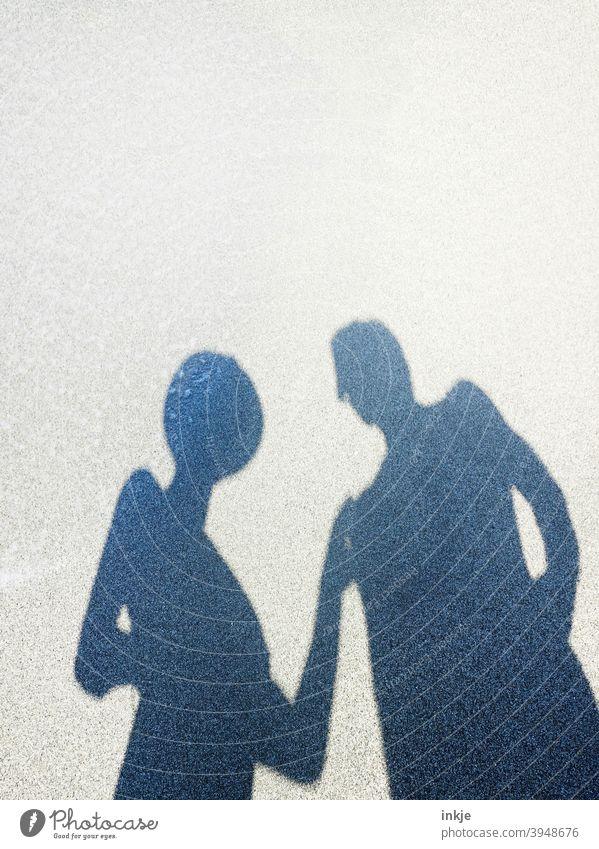 Dialog am Strand Schatten Silhouette Paar Gespräch Kommunikation Sommer Sonne Urlaub Ferien Sommerurlaub Hut Strohhut Textfreiraum Mann und Frau Tourismus