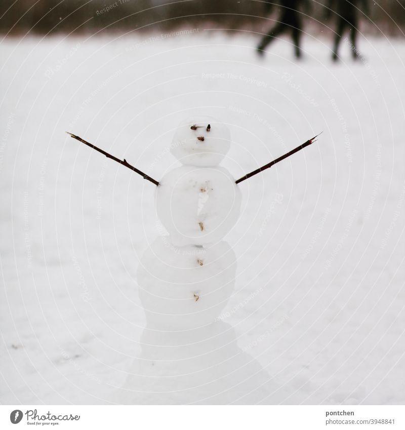 Ein Schneemann mit ausgestreckten Armen steht im Schnee. Verschwommene Spaziergänger im Hintergrund. Winter schnee winter kinderspiel freude spaß vergnügen kalt