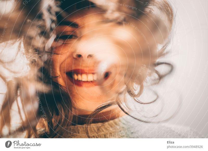 Frau mit langen Haaren guckt vornübergebeugt in die Kamera und lächelt Lächeln Selfie Lange Haare lachen gute Laune Freude reingucken authentisch Fröhlichkeit