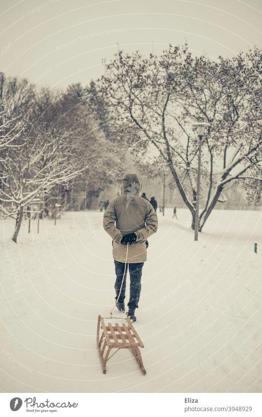 Ein Mann zieht einen Schlitten durch den Schnee. Winterstimmung. ziehen Landschaft Holzschlitten Winterlandschaft Schneelandschaft kalt draußen Natur Bäume
