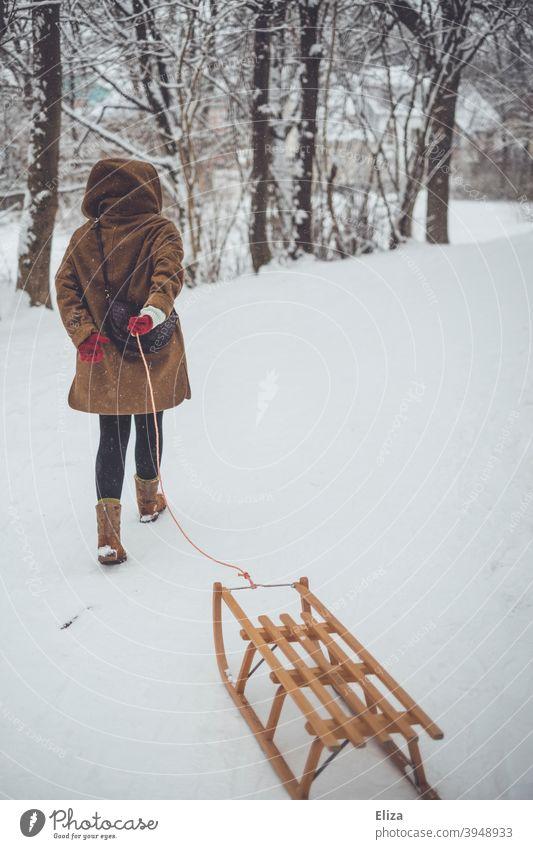 Eine Frau zieht einen Schlitten durch den Schnee. Winterstimmung. ziehen Landschaft Holzschlitten Winterlandschaft Schneelandschaft kalt draußen Natur Bäume
