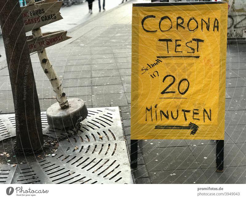 Wegweiser zum Corona-Test mit Ergebnis innerhalb von 20 Minuten. Foto: Alexander Hauk Schild gelb Aufsteller Passantenstopper Außenaufnahme Zeit Krankheit