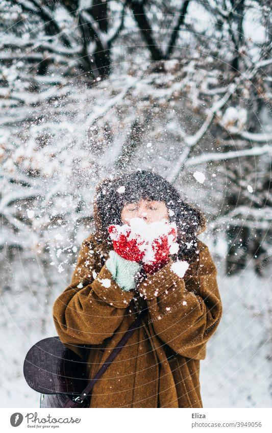 Frau pustet Schnee im Winter Freude Schneelandschaft verschneit Natur draußen kalt weiß Winterstimmung Winterwald Wintertag Handschuhe Mantel jung winterlich